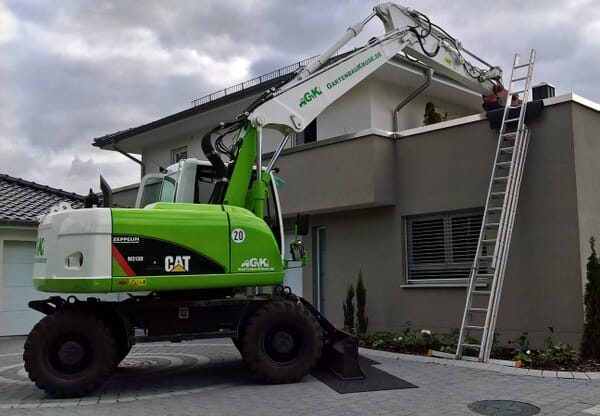 Mobilbagger hebt Baumaterial auf Dachterasse